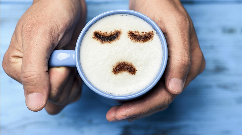 Depressive Störung: Ein Mann hält eine blaue Tasse mit Cappuccino, in dessen Schaum ein trauriges Smiley zu sehen ist.