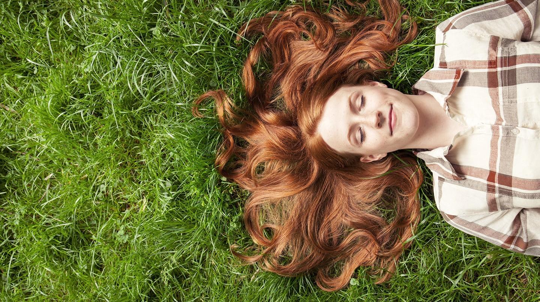 Gesunde Haut und Haare: Eine Frau liegt auf dem Rasen, die kräftigen, glänzenden Haare sind um den Kopf ausgebreitet.