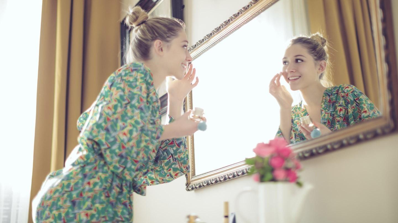 Beauty-Routine: Junge Frau in grünem Kleid steht vor einem Spiegel und cremt sich ein.