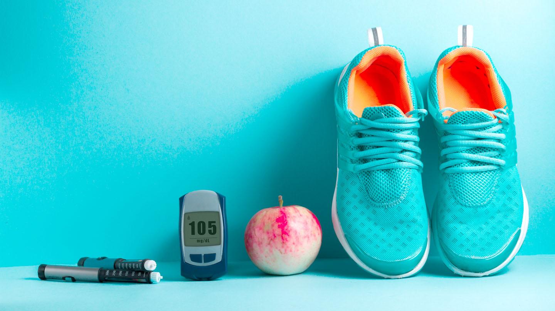 Diabetes und Corona: Insulinpen, Blutzuckermessgerät, Apfel und Turnschuhe nebeneinander aufgereiht.