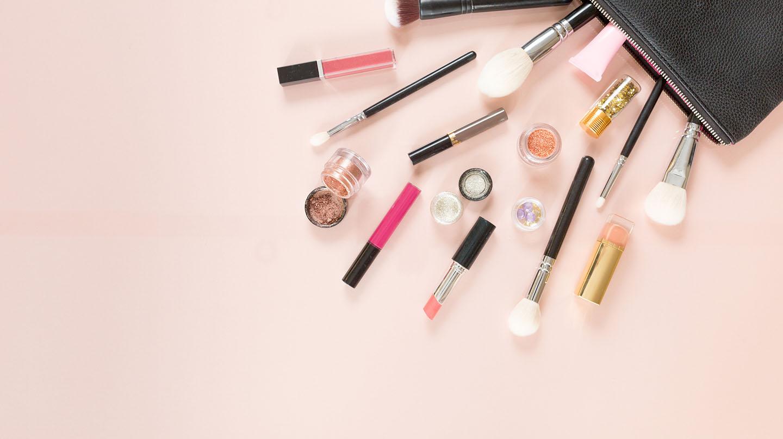 Kosmetik ausmisten: Vor einer geöffneten schwarzen Kosmetiktasche auf lachsfarbenem Grund liegen Kosmetikartikel wie Lippenstifte, Pinsel und Lidschatten